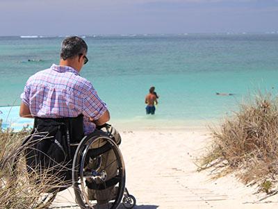 Man in rolstoel op een zomers strand, zee op de achtergrond