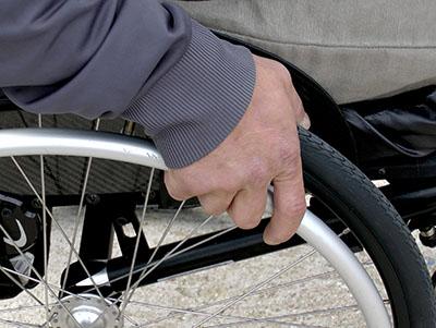 Close-up van hand van een man op het wiel van zijn rolstoel