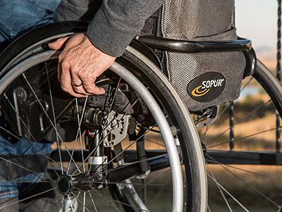 Zijkant van rolstoel, hand van de man op het wiel
