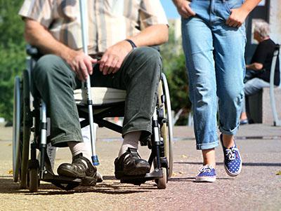 Man met stok in in rolstoel, meisje loopt ernaast