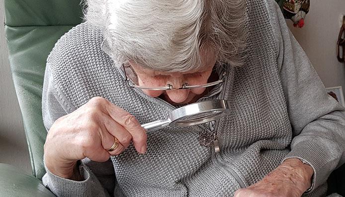 Oudere dame leest met een vergrootglas