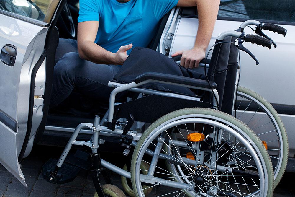 Man met rolstoel stapt in de auto