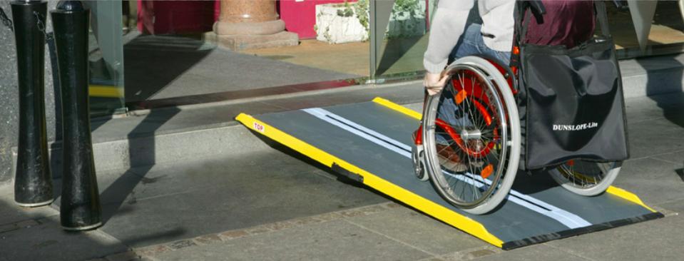 Iemand in een rolstoel rijdt over een verplaatsbare oprijplaat