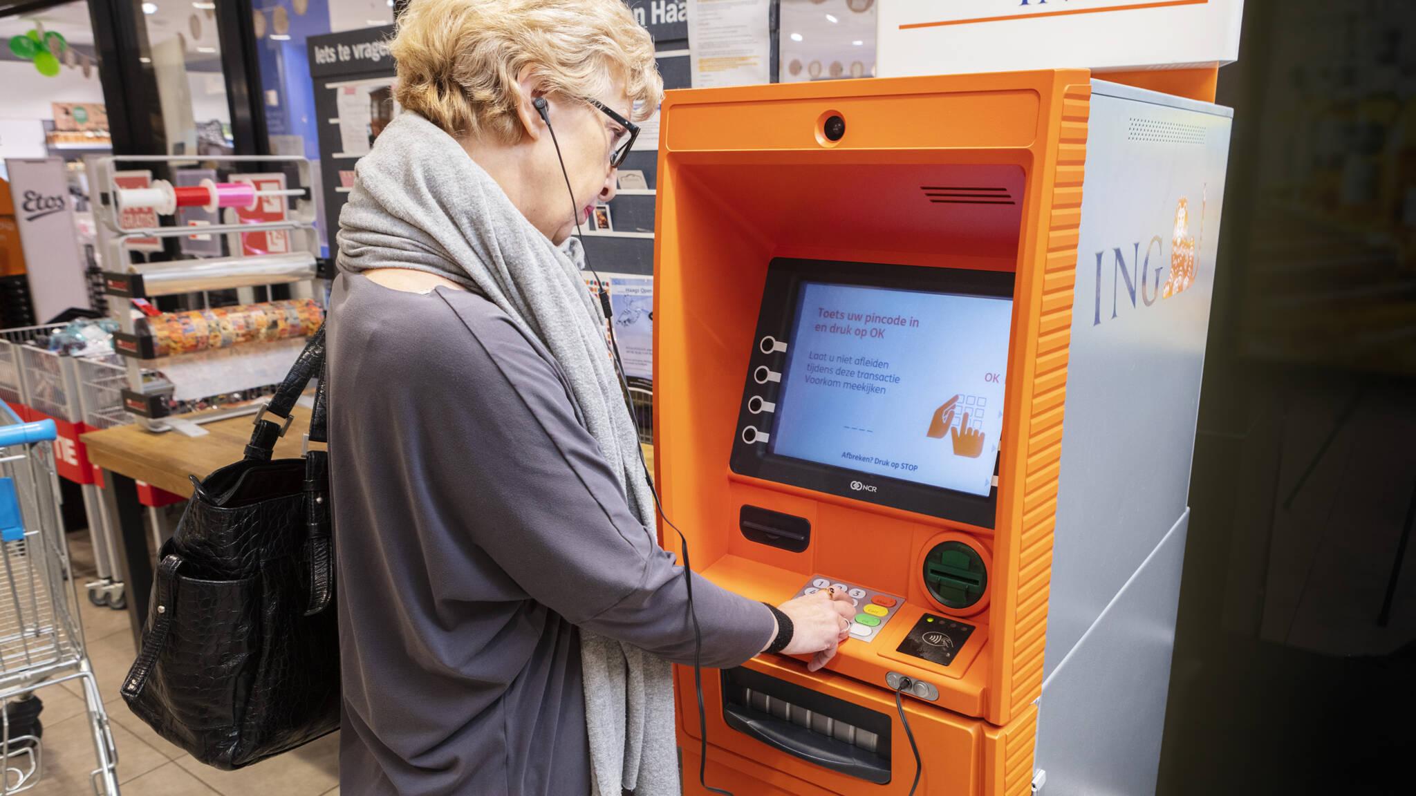 Foto van een dame bij een pinautomaat