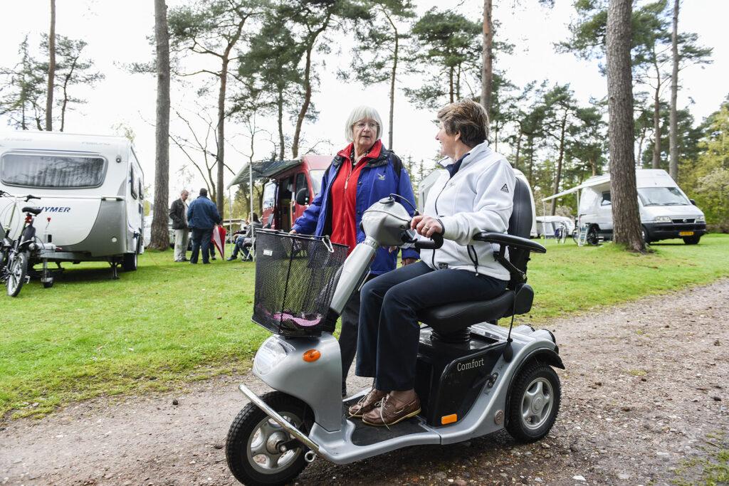 Foto van twee pratende dames waarvan een in een rolstoel