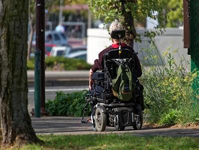 Foto van de achterkant van een dame in een electrische rolstoel