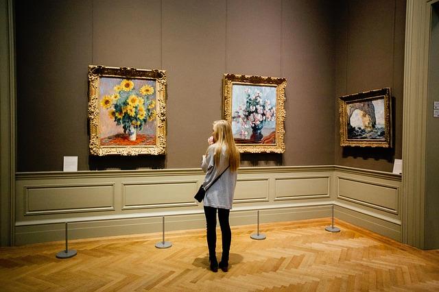 Foto van een vrouw in een museum voor een schilderij