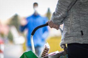 Foto van een persoon met een winkelmandje in de hand