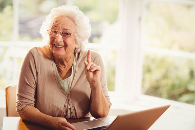 Foto van lachende oudere vrouw met een laptop
