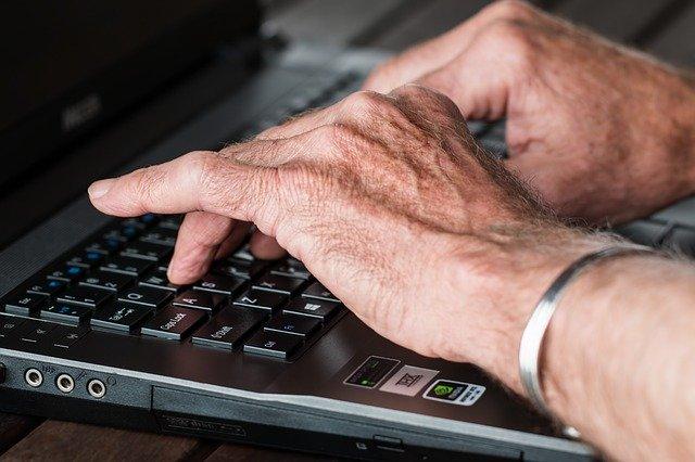 Foto van oudere handen op een laptop