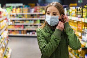 Foto van een jonge vrouw met mondkapje in een winkel