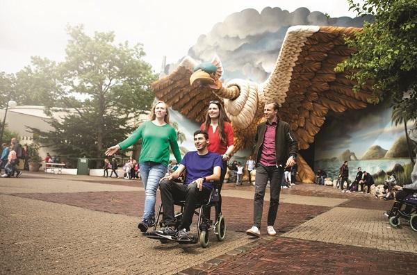 Foto van 4 personen waarvan 1 persoon in een rolstoel voor de Vogelrok