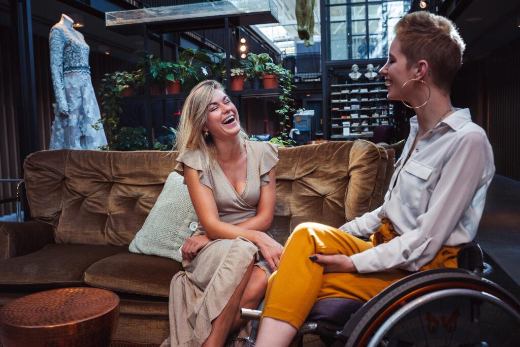 Foto van twee lachende jonge vrouwen, 1 op een bank, 1 in een rolstoel