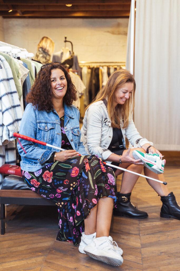 Foto van een dame met een geleidenstok zitten in ene winkel