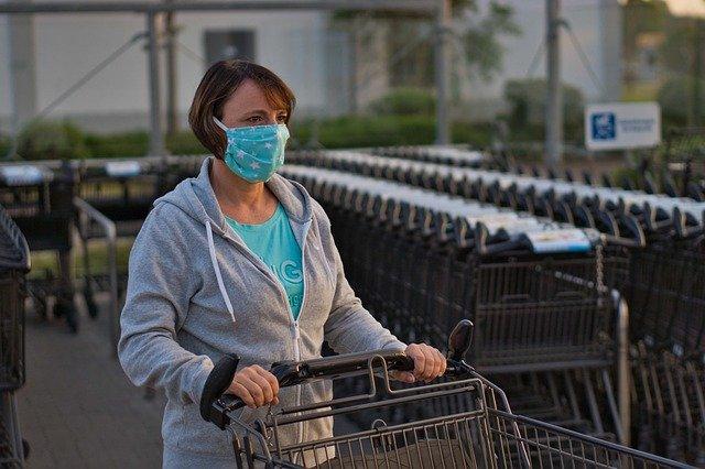 Foto van een dame met een mondkapje op achter een winkelwagen
