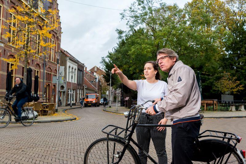 Foto van een man op de fiets en een meisje die hem de weg wijst