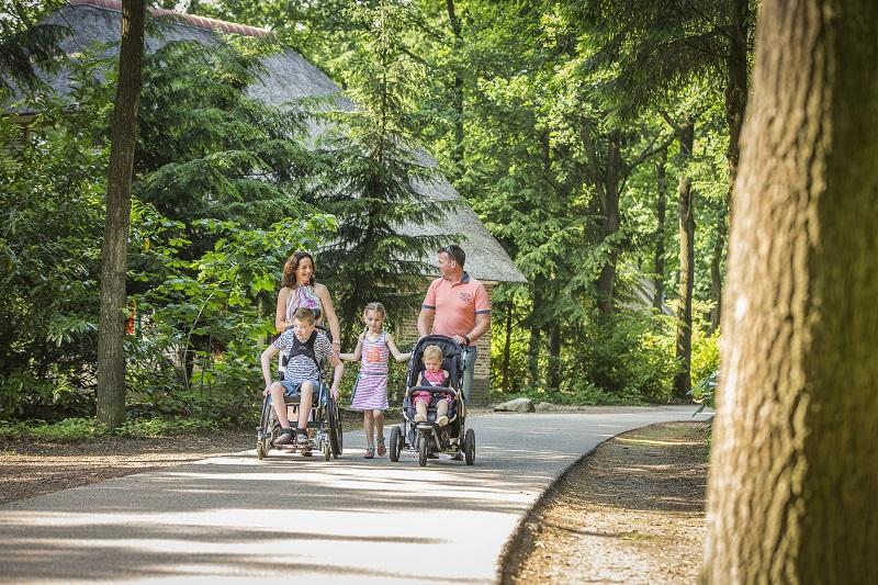 Foto van een wandelend gezin met een kind in een rolstoel