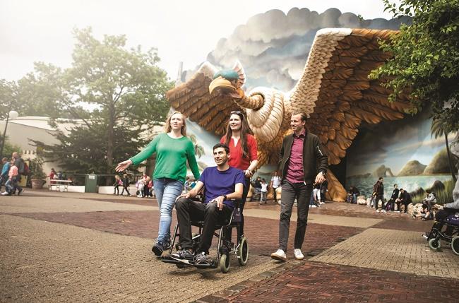 Foto van 4 personen voor de VogelRok in de Efteling, een persoon zit in een rolstoel