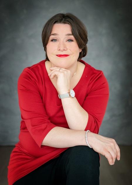 Portretfoto van Marianne Dijkshoorn, ze glimlacht en draagt een rode trui