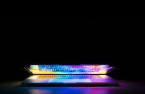 Foto van een zwarte achtergrond met een laptop waar gekleurd licht uit schijnt